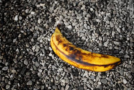 angeschlagene Banane im Dreck: weggeworfen