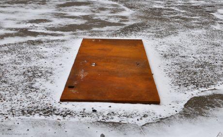 Farbfleck im Winter: rostende Eisenplatte