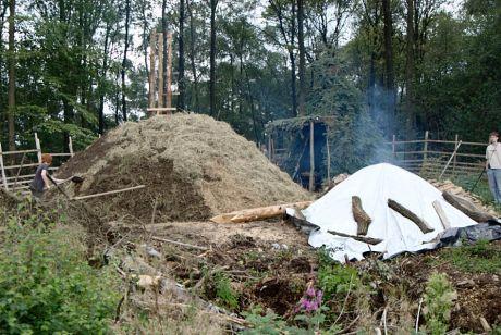 der Meilerbau ist fast vollendet: der mit Stroh abgedeckte Meiler wird derzeit mit Erde (Grassoden) abgedichtet