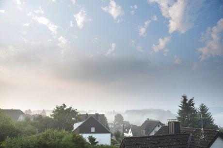 Ein Dorf entsteigt dem Morgennebel