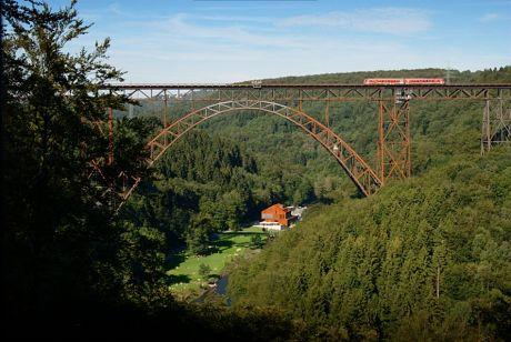"""Müngstener Brücke über dem Brückenpark: samt dem roten Triebwagenzug, der sich """"Müngstener"""" schimpft"""