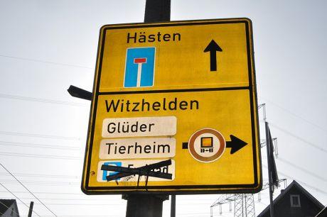 zugeklebte Hinweis auf das Freibad bzw. den Parkplatz: Vorwegweiser auf das Schwimmbad Schellbergtal im Bereich Pfaffenberger Weg