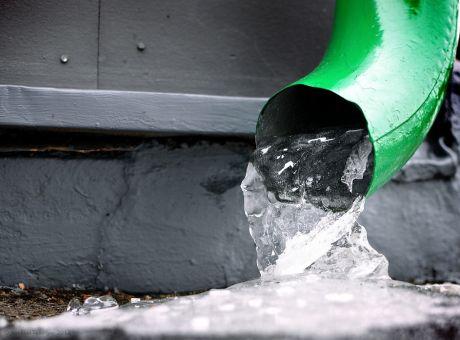 die sich auf die Straße ergießende Regenrinne: im Winter entschleunigt