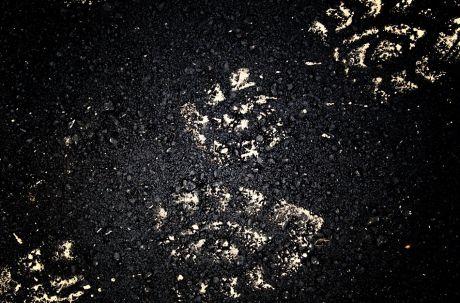 Spuren im Sand sind es nicht: eher Sand auf Bitumen